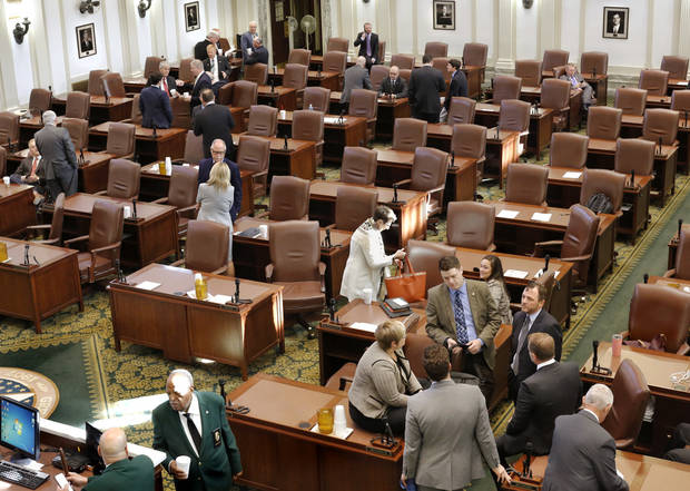 After the House adjourned from its scheduled business Friday morning, Oct. 27, 2017, several lawmakers remained in the chamber and visited in smaller groups. Democrat legislators huddle at bottom right while Republican members gather on the left side of the room. Photo by Jim Beckel, The Oklahoman