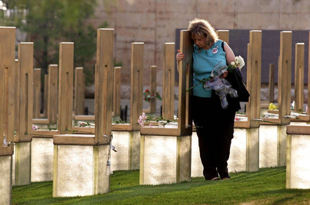 ALFRED MURRAH FEDERAL BUILDING CAR BOMB EXPLOSION, BOMBING, ANNIVERSARY: Oklahoma City National Memorial: Ginny Moser places flowers and hugs memorial chairs at the April 19, 2002 ceremony. Staff photo by Steve Sisney