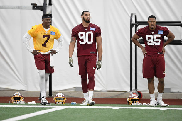 Washington Redskins quarterback Dwayne Haskins Jr. (7) stands on the field next to linebacker Montez Sweat (90) and linebacker Jordan Brailford (95) during an NFL football rookie camp, Saturday, May 11, 2019, in Ashburn, Va. (AP Photo/Nick Wass)