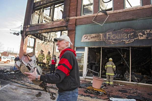 Fiddle player Byron Berline carries out damaged items from his Double Stop Fiddle Shop, which was destroyed by a Feb. 23 fire in Guthrie, Okla. on Monday, Feb. 25, 2019. The fire on Saturday destroyed two businesses in historic downtown Guthrie. Photo by Chris Landsberger, The Oklahoman Archives