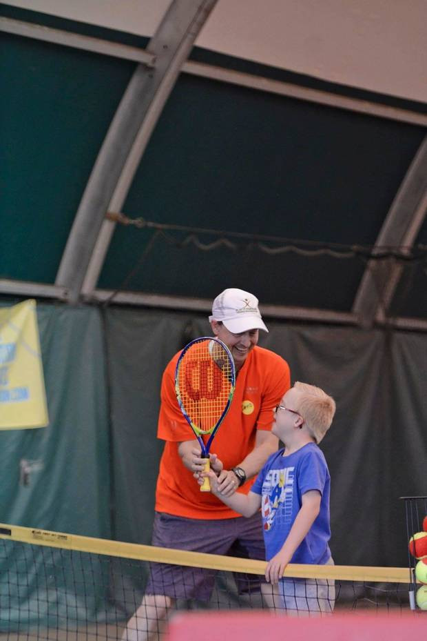 David Minihan teaches Kasen Gilbreath how to hold his racket during the We Are Champions Tennis Clinic at Kickingbird Tennis Center in Edmond. [PHOTO PROVIDED]