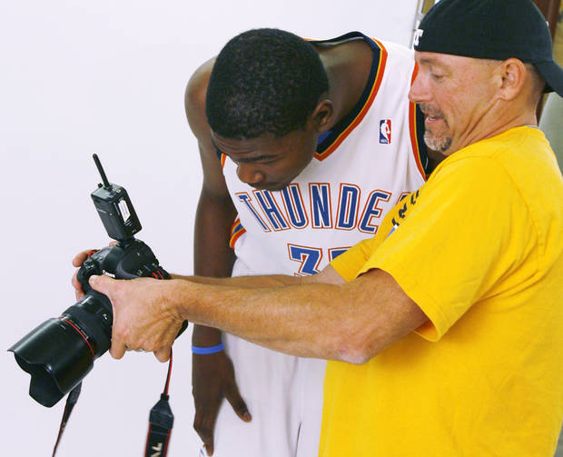 Photographer Layne Murdoch shows Kevin Durant a photo during media day for the Thunder at the Skirvin Hilton hotel in Oklahoma City in 2008. BY NATE BILLINGS, THE OKLAHOMAN.