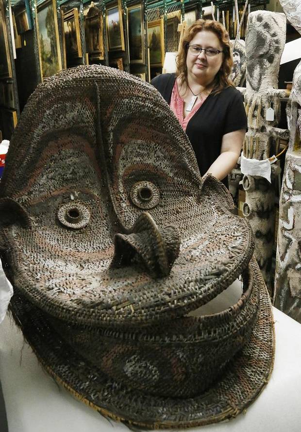 Delaynna Trim, Curator of Collections at the Mabee-Gerrer Museum of Art in Shawnee, looks at a recent acquisition, a large decorative mask from Papua New Guinea, Friday, Aug. 9, 2019. The museum is celebrating its 100th anniversary in 2019. [Jim Beckel/The Oklahoman]