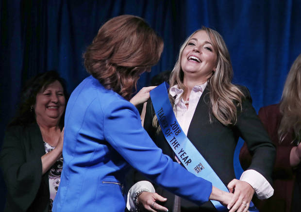 "Joy Hofmeister, left, state superintendent of schools, places the ""Teacher of the ""Year"" sash on newly named Teacher of the Year Rebecca Oglesby, right, an elementary school teacher from Yukon, Okla., Tuesday, Sept. 18, 2018, in Oklahoma City. (AP Photo/Sue Ogrocki)"