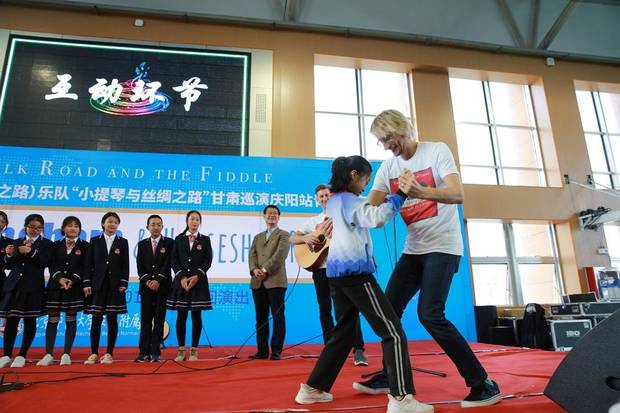 Oklahoma musician Kyle Dillingham teaches children how to two-step at Beijing Normal University. [Photo by Yunfan Photography]