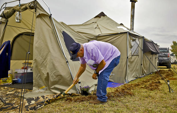 "Nicky Jones, 66, of Quincy, Ill., prepares his camp site for rain at the ""Feast of the Tabernacles"" event at Bell Cow Lake in Chandler. [Photo by Chris Landsberger]"