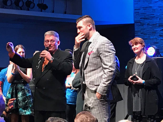 "Robert Miller, chairman of ""Night to Shine OKC,"" stands on the stage with Tim Tebow at the prom-night event on Friday, Feb. 9, at Putnam City Baptist Church in Oklahoma City. [Photo by Carla Hinton, The Oklahoman]"