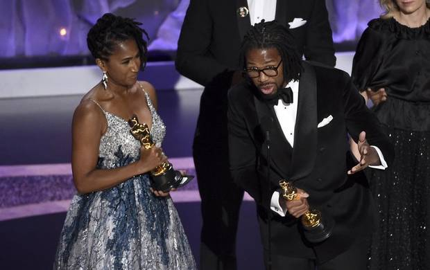 "Karen Rupert Toliver, left, and Matthew A. Cherry accept the award for best animated short film for ""Hair Love"" at the Oscars on Sunday, Feb. 9, 2020, at the Dolby Theatre in Los Angeles. [AP Photo/Chris Pizzello]"