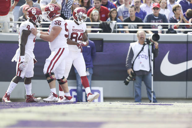 Oklahoma Sooners offensive lineman Creed Humphrey (56) and Oklahoma Sooners wide receiver Lee Morris (84) celebrate with Oklahoma Sooners running back Trey Sermon (4) after his touchdown during the NCAA football game between the TCU Horned Frogs and the Oklahoma Sooners at Amon G. Carter Stadium in Fort Worth, Texas on Saturday, October 20, 2018. IAN MAULE/Tulsa World