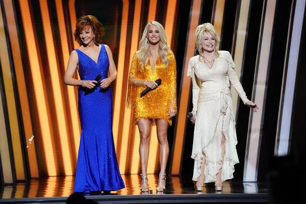 Carrie Underwood, center, with special guest hosts Dolly Parton, right, and Reba McEntire, host the 53rd Annual CMA Awards live from Bridgestone Arena in Nashville Wednesday, November 13 on ABC. [John Russell/CMA]