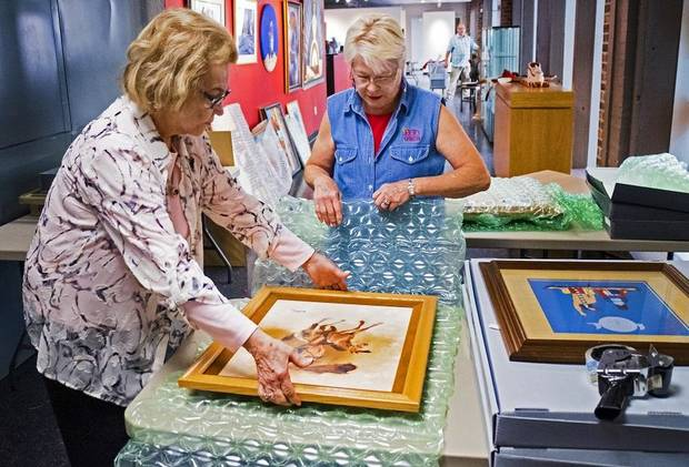 Lou Kerr and Teri Stanek, from left, work to pack artwork at the Red Earth Art Center in Oklahoma City, Okla. on Thursday, May 16, 2019. The center is relocating to ground floor of BancFirst Tower. [Chris Landsberger/The Oklahoman]