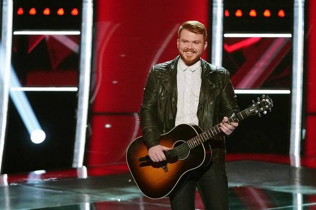 Trey Rose holding a guitar in his hand with a smile on his face on the stage of The Voice