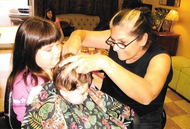 Reed cutting the hair of one of her grandchildren. Photo provided.