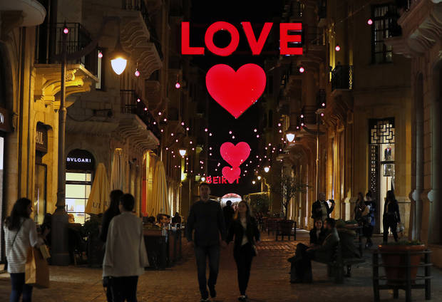 Lebanese citizens walk by Valentine's Day decorations, in downtown Beirut, Lebanon, Friday, Feb. 9, 2018. (AP Photo/Hussein Malla)