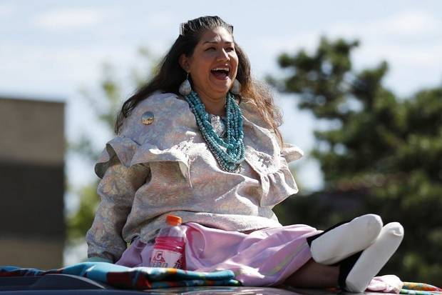 Tamara Francis, chairman for the Caddo Nation of Oklahoma, laughs as she rides on top of a car during the 2019 Red Earth Festival Parade in downtown Oklahoma City, Oklahoma Saturday, June 8, 2019. [Paxson Haws/The Oklahoman]