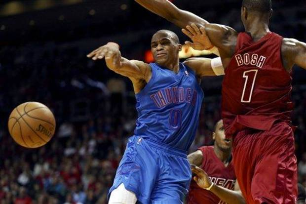 Miami Heat's Chris Bosh (1) pressures Oklahoma City Thunder's Russell Westbrook (0) into a pass during the second half of an NBA basketball game in Miami, Tuesday, Dec. 25, 2012. The Heat won 103-97. (AP Photo/J Pat Carter)