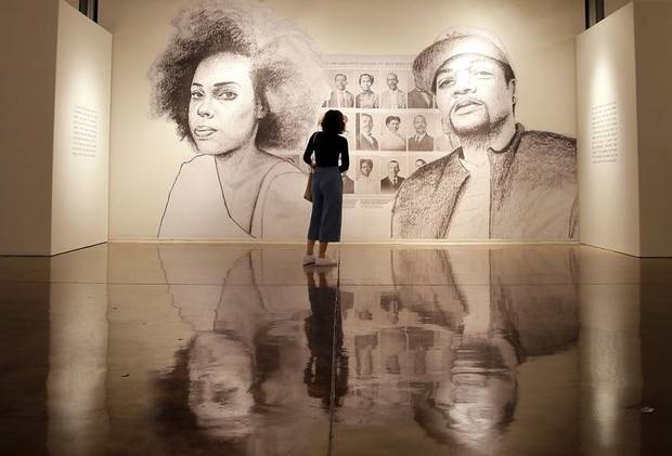 "A person looks at ""Progressive Citizens,"" a large-scale paper and wheatpaste installation by artist Tatyana Fazlalizadeh. It is part of her exhibit ""Oklahoma Is Black,"" a depiction and celebration of Oklahoma City's rich black history, on Feb. 21 at Oklahoma Contemporary in Oklahoma City. [Bryan Terry/The Oklahoman]"