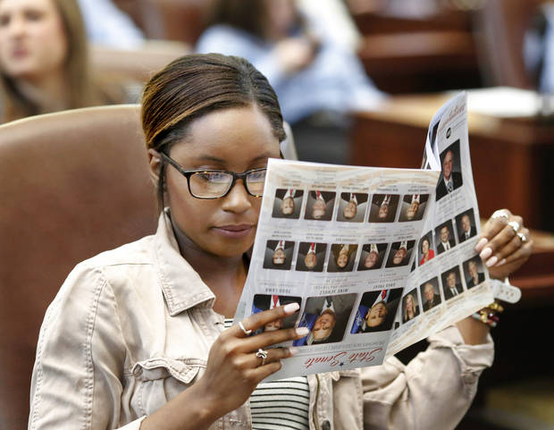Ryleigh Cooper, a senior from Ada attending East Central University, studies the faces and names on a legislative directory in February during Higher Education Day at the state Capitol. [Photo by Jim Beckel, The Oklahoman]