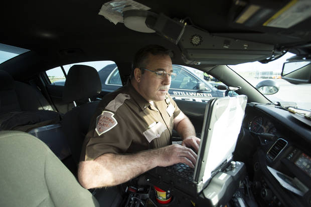 Trooper Joe Williams checking information during a recent ENDUI checkpoint. Photo: J Pat Carter