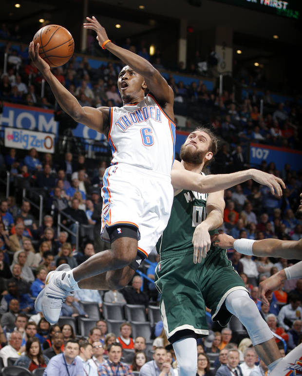 Semaj Christon drives past Milwaukee's Spencer Hawes for a basket Tuesday night