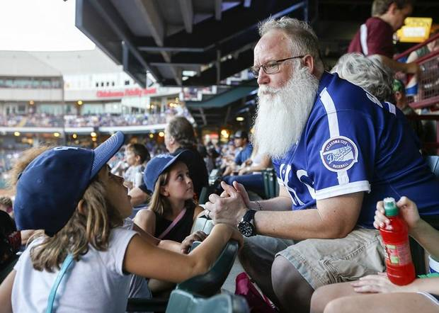 Ron Herendeen, known as Santa Ron, talks with Teagan Taylor, 6, as he and his Team Santa kids attend an Oklahoma City Dodgers baseball game at the Chickasaw Bricktown Ballpark in Oklahoma City, Friday, Aug. 24, 2018. Team Santa is a program to promote health and fitness in youngsters that Santa Ron started after he was diagnosed with Type 2 diabetes. Photo by Nate Billings, The Oklahoman