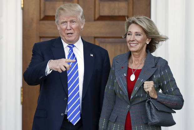 FILE – In this Nov. 19, 2016 file photo, President-elect Donald Trump, left, and Betsy DeVos, right, pose for photographs at Trump National Golf Club Bedminster's clubhouse in Bedminster, N.J. Republican Ohio Gov. John Kasich wrote a Jan. 24, 2017, letter urging confirmation of DeVos, Trump's education secretary nominee, without mentioning the significant unpaid fine owed to Ohio by a now-defunct political action committee she controlled. (AP Photo/Carolyn Kaster, File)