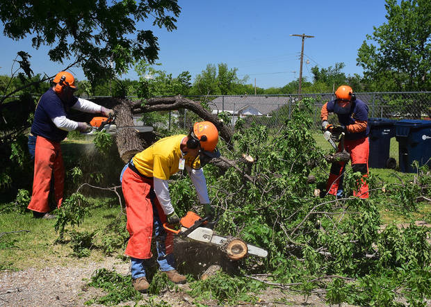 Men clear downed trees in Oklahoma City following severe weather that affected the metro. [Photo by  David Crowell]