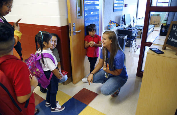 Kindergarten teacher Kyrianna Mitchell kneels to welcome Reina Camargo to her classroom as she arrives with her family on the first day of school at Cesar Chavez Elementary School on SE Grand Blvd. Students returned to classrooms across the city on Wednesday, Aug. 1, 2018, as Oklahoma City Public Schools started another school year. Photo by Jim Beckel, The Oklahoman