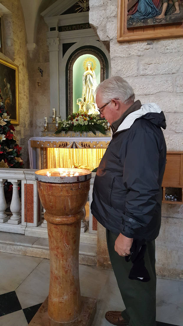 The Rev. Steve Graham with Oklahoma Cooperating Baptists lights a candle in the Roman Catholic Church of St. Catherine inside the Church of the Nativity in Bethlehem. [Photo by Carla Hinton, The Oklahoman]
