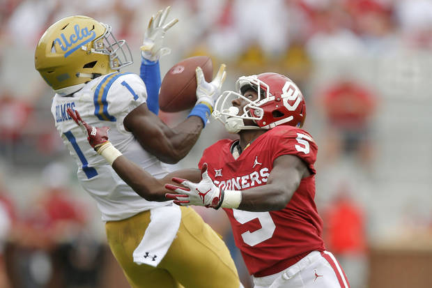 UCLA's Darnay Holmes intercepts a pass intended for OU's Marquise Brown last season in Norman. (Photo by Bryan Terry)