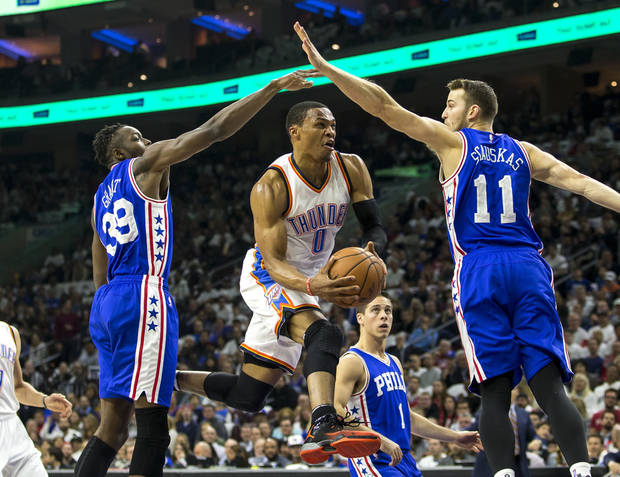 Russell Westbrook splits Sixers Nik Stauskas and Jerami Grant on Wednesday night. (AP Photo)