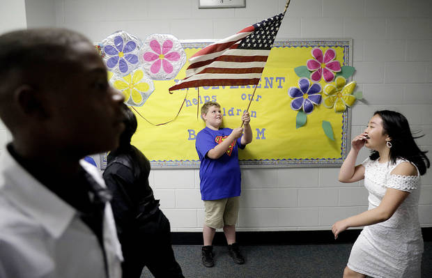 Nick Murry, a third grader, waves a flag as he congratulates sixth graders Larontae Clayton, left, Jacqueline Vang and others during their final walk through on their way to the sixth grade promotion exercises on the last day of school at Lewis and Clark Elementary School, Thursday, May 31, 2018, in Tulsa, Okla. (Mike Simons/Tulsa World via AP)