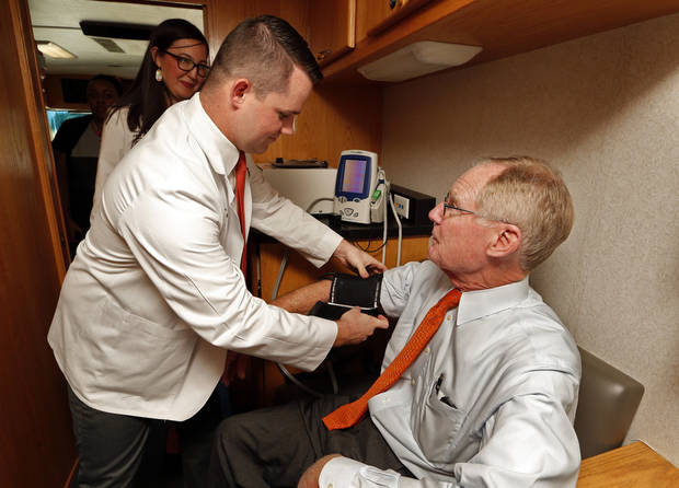 Medical Student Matthew Else takes OSU President Burns Hargis' blood pressure inside the Mobile Telemedicine Clinic in 2015 after an announcement by Gov. Mary Fallin and Hargis about a $3.8 grant from the tobacco trust to bring doctors to underserved, rural areas. [Photo by Steve Sisney, The Oklahoman]