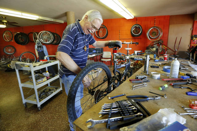 Larry Batten, Chain Reaction Ministries coordinator, refurbishes bicycles at First Christian Church of Oklahoma City to give away to those who need them. [Photo by Jim Beckel, The Oklahoman]